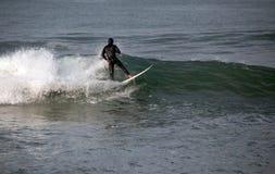 Surfare på våg på sandbaren var Santa Clara River tömmer in i Stilla havet på Ventura California U arkivbild