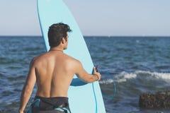 Surfare som bakifrån bär hans blåa surfingbräda Royaltyfri Foto