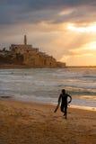 Surfare som dyker upp på solnedgången - gamla Jaffa, Israel - som är medelhavs- Royaltyfria Foton