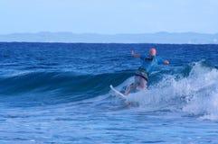 Surfare som fångar en liten våg på den Stradbroke ön Royaltyfria Bilder