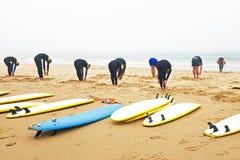Surfare som gör övningar Fotografering för Bildbyråer