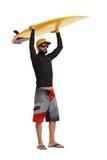 Surfare som rymmer en surfingbräda ovanför hans huvud royaltyfri fotografi
