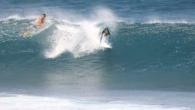 Surfare som surfar en trevlig våg i Hawaii arkivfilmer
