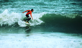 Surfare som surfar på havet med den orange våta dräkten fotografering för bildbyråer