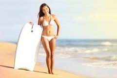 Surfarebikinikvinna på stranden som ler med surfboar Royaltyfri Fotografi