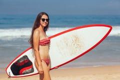 Surfareflicka i röda bikinier som går med surfingbrädan på den sandiga stranden härligt kvinnabarn för strand konkurrensar som dy Fotografering för Bildbyråer