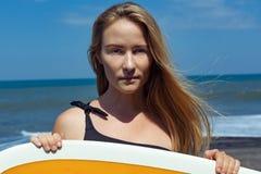 Surfareflicka på den tropiska stranden arkivfoton
