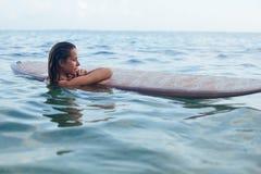 Surfareflickan på surfingbrädan har en gyckel, innan han surfar royaltyfria bilder