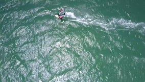 Surfarekamper med vind- och havvågor lager videofilmer
