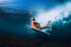 Surfarekvinna med den undervattens- surfingbrädadyken royaltyfria foton