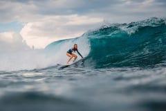 Surfarekvinna och stor blå våg royaltyfria bilder