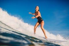 Surfarekvinna på surfingbrädaritten på havvåg Kvinna i havet under att surfa royaltyfri bild