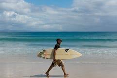 Surfaren går i stranden av Byron Bay Arkivfoton