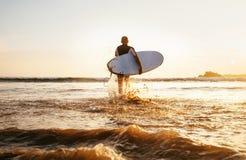 Surfaren kör med surfingbrädan in mot tid för solnedgång för ta för havvågor Royaltyfri Fotografi