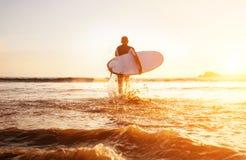 Surfaren kör med surfingbrädan in mot tid för solnedgång för ta för havvågor fotografering för bildbyråer