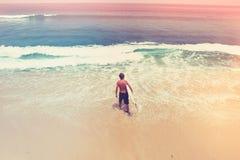 Surfaren med ettbräde går till havet _ tappning för stil för illustrationlilja röd Arkivbilder