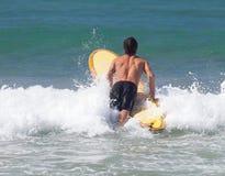 Surfaren på longboard rider en våg i havet arkivbilder
