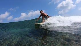 Surfaren rider den kristallklara havvågen arkivfilmer