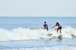 Surfaren rider den tillbaka sidan av en våg Royaltyfria Bilder