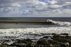 Surfaren surfar en perfekt våg på en solig dag Arkivbilder