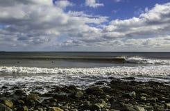 Surfaren surfar en perfekt våg på en solig dag Arkivbild