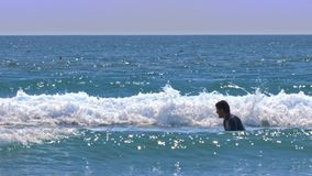 Surfarenybörjareförsök att fånga vågen under solsken lager videofilmer