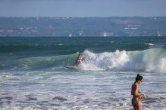 Surfareridningvåg och en kvinna på forgrounden på Echo Beach Ca royaltyfria foton