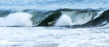 Surfboad está ainda na vista enquanto uma onda traga um surfista imagem de stock