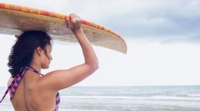 Surfboard нося женщины на голове на пляже Стоковые Изображения RF