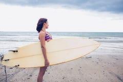 Surfboard нося женщины на пляже Стоковые Фотографии RF