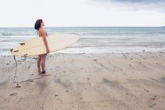 Surfboard нося спокойной женщины на пляже Стоковая Фотография RF