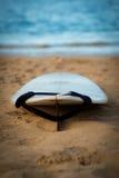Surfboard с поводком на песке с океаном в предпосылке Стоковые Изображения RF
