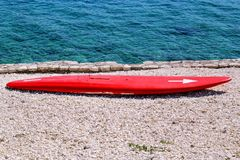 Surfboard on the beach awaiting fun in the sun. A red surfboard on the waves, on the beach by the sea. Beach landscape with surfboard on the sand. Surfboard on Royalty Free Stock Photos