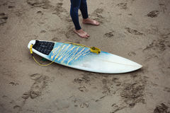 Surfboard on the beach next to the surfer legs. Royalty Free Stock Images