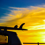Surfboard on a car roof at sunset Stock Photos