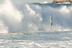 Surfboard flying in front of breaking wave Royalty Free Stock Photography