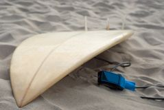Surfboard lying on beach. Surfboard on beach lying on sand having a break from surfing Royalty Free Stock Photo