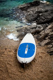 Surfboard lying on sand beach next to wavy sea Stock Image