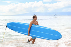 Surfboard man surfer coming out of surfing waves. Surfing man surfer coming out of waves with blue long surfboard. athletic guy all wet after a surf session royalty free stock images