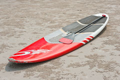 Surfboard and oar on the sand at the beach Stock Photos