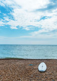 Surfboard on the pebble beach and the ocean, waves and blue sky Stock Photo