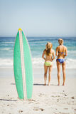 Surfboard in sand and rear view of two women looking at sea Royalty Free Stock Photo