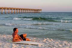 Surfboarder Relaxs On Beach. Young handsome adult surfer sits on the beach leaning on his surfboard with a pier in the background on Pensacola Beach, Florida Stock Photo