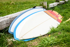 Surfboards stacked and leaned against wooden fence laying on gro Stock Photo