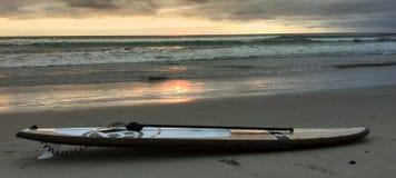 Surfbrett auf dem Sand bei Sonnenuntergang Lizenzfreie Stockbilder
