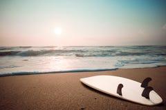 Surfbrett auf tropischem Strand bei Sonnenuntergang im Sommer stockfotos