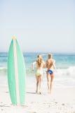 Surfbrett im Sand und in zwei hinteren Frauen, die auf dem Strand laufen Lizenzfreie Stockfotos