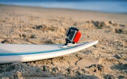 Surfbrett mit befestigter Aktionskamera liegt auf dem Sand Stockbild
