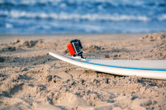 Surfbrett mit befestigter Aktionskamera liegt auf dem Sand Lizenzfreie Stockbilder