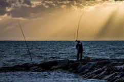 Surfcaster dans le coucher du soleil image libre de droits